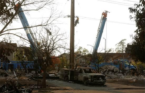 עובדי PG&E מטפלים בעמוד חשמל שקרס / צילום: ג'ים אורקוהרט, רויטרס