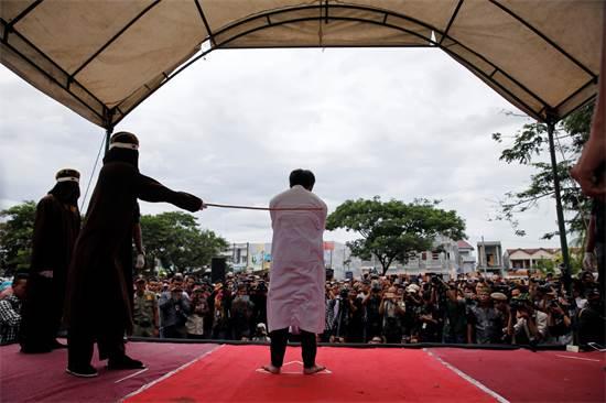 גבר אינדונזי מולקה בפומבי כעונש על קיום יחסי מין עם גבר אחר בכיכר העיר בנדה אצ'ה שבמערב המדינה, מאי 2017 / צילום: Beawiharta, רויטרס