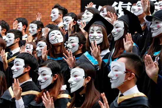 סטודנטים בהונג-קונג מביעים את תמיכתם במחאה נגד חוק ההסגרה בטקס הסיום באוניברסיטה הפוליטכנית, אוקטובר 2019 / צילום: Tyrone Siu, רויטרס