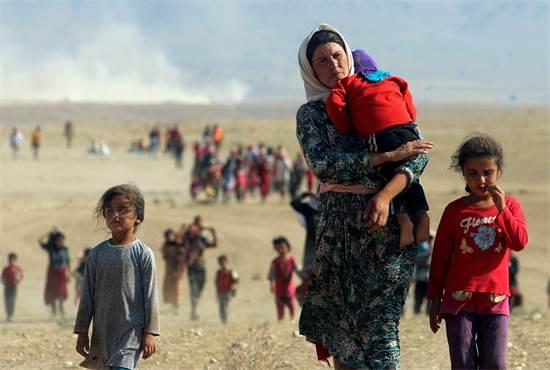 """בנות משפחה יזידית בורחות מפני לוחמי המדינה האסלאמית אל עבר הגבול עם סוריה לאחר """"טבח סינג'אר"""", אוגוסט 2014 / צילום: Rodi Said, רויטרס"""