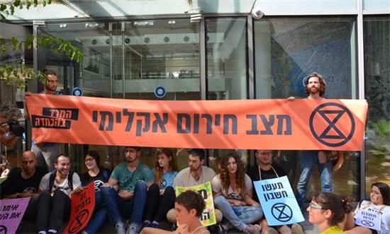 """מייצג מחאה של תנועת המרד בהכחדה ליד מתחם בורסת ת""""א / צילום: איילה טולקין, יח""""צ"""