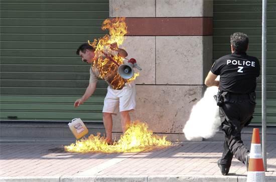 מפגין יווני רגע אחרי שהצית עצמו מחוץ לסניף הבנק שלו בסלוניקי, לאחר שבקשתו לקבל הלוואה סורבה, ספטמבר 2011 / צילום: Nodas Stylianidis, רויטרס