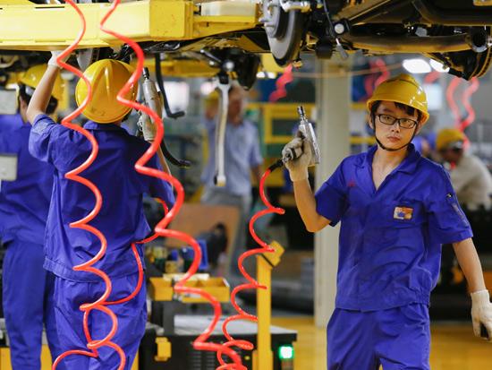 פועלים במפעל בשנזן / צילום: REUTERS Bobby Yip