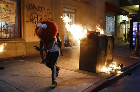 מפגין עם מסכה של הבובה אלמו מרחוב סומסום האמריקאי רוקד בהפגנה בפילדלפיה ביום שבת / צילום: Matt Rourke, AP