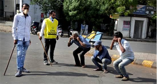 שוטר הודי גורם לאזרחים לבצע כפיפות כעונש על יציאה החוצה ללא סיבה טובה / צילום: אג'יט סולאנקי, AP