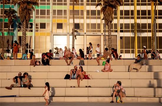 אנשים יושבים בטיילת בתל אביב ליד חוף הים בזמן גל החום / צילום: Oded Balilty, AP