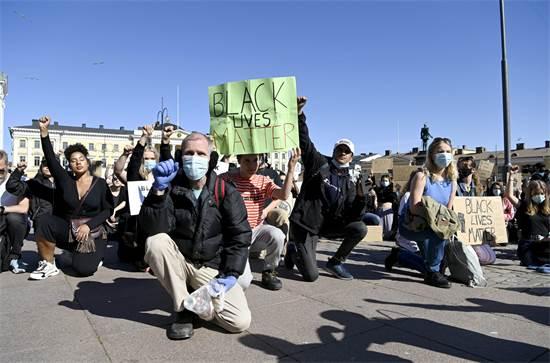 מפגינים כורעים ברך בהפגנה בהלסינקי, בפינלנד / צילום: Lehtikuva/Antti Aimo-Koivisto, רויטרס