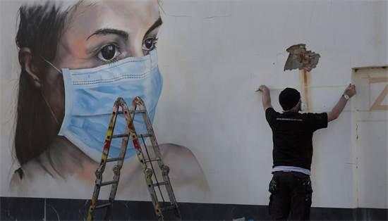 אמן רחוב מצייר על קיר בבלגיה / צילום: Virginia Mayo, AP