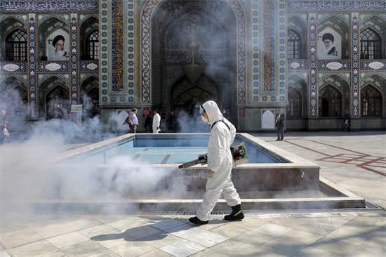 כבאי מחטא את רחבת המסגד ב-6 במרץ 2020 / צילום: Ebrahim Noroozi, AP
