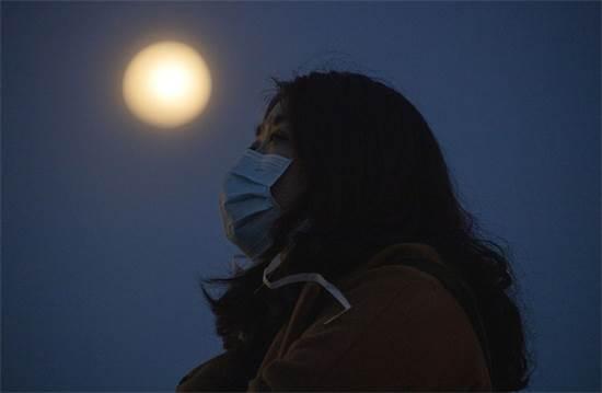 אישה הנושאת מסיכה נגד וירוס הקורונה מרימה את עיניה ליד הירח המלא בווהאן שבמרכז מחוז הוביי בסין / צילום: AP