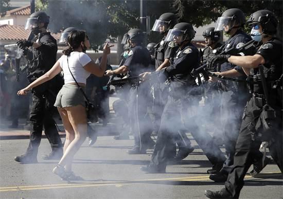 מפגינה נעמדת מול משטרת סן חוזה בקליפורניה ששועטים אל עבר שורת המפגינים, ביום שישי / צילום: Ben Margot, AP