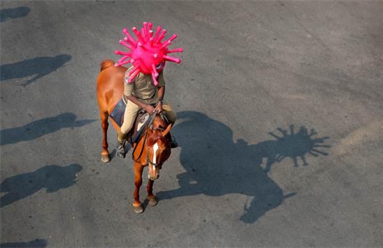 שוטר הודי רוכב על סוס ולראשו קסדה בצורת נגיף הקורונה / צילום: Mahesh Kumar A., AP