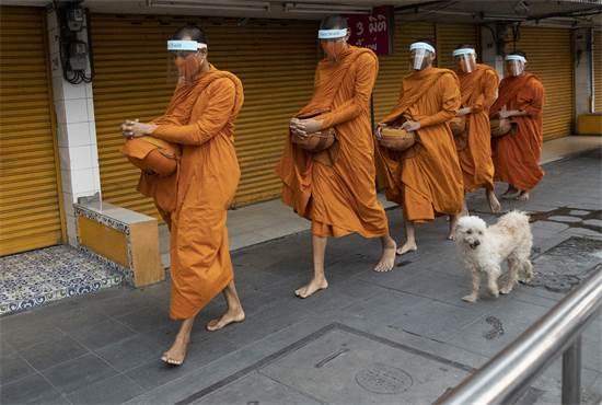 נזירים בודהיסטים תאילנדים מסתובבים בבנגקוק עם מסכות הגנה מפני הקורונה / צילום: Sakchai Lalit, AP
