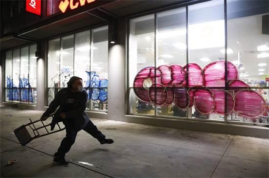 מפגין רגע לפני שהוא מנפץ חנות בלוס אנג'לס ביום שבת / צילום: Jae C. Hong, AP