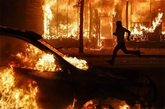 מפגין חולף על פני מכוניות ובניינים בוערים שהוצתו על ידי המוחים נגד הרצח של פלויד בידי המשטרה ביום שבת   / צילום: John Minchillo, AP