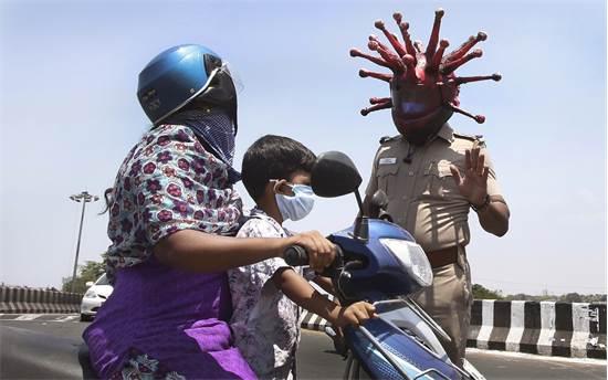 שוטר עם קסדה בצורת נגיף הקורונה מבקש מאנשים בהודו לחזור לביתם / צילום: R. Parthibhan, AP