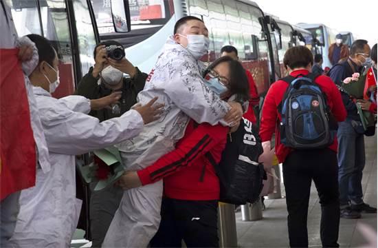 אישה בווהאן קופצת על עמית לעבודה ביום הראשון לשחרור לאחר הסגר / צילום: AP