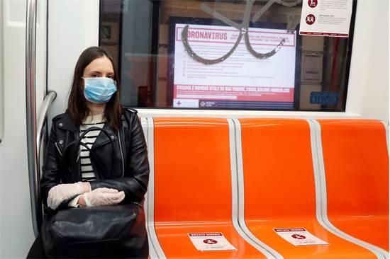 אישה עוטה מסכה ברכבת התחתית ברומא, איטליה. הנוסעים נדרשים לשמור על מרחק זה מזה / צילום: Remo Casilli, רויטרס