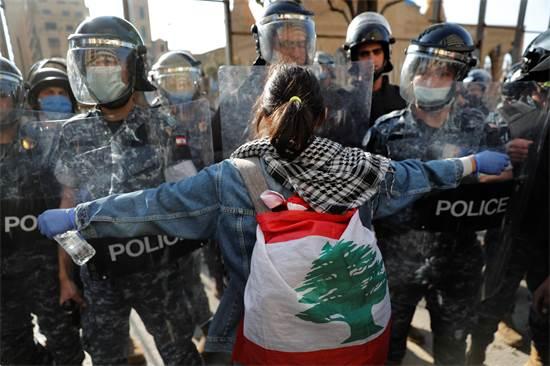 מגפינה בלבנון עומדת מול חיילים שעוטים מסכות בשל הקורונה / צילום: Hussein Malla, AP