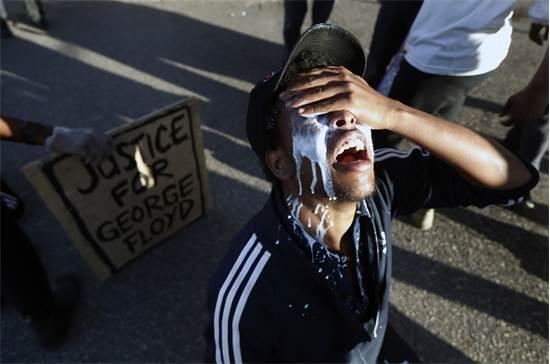 מפגין שוטף את העיניים בחלב לאחר שנפגע מגז מדמיע במיינאפוליס ביום שישי / צילום: John Minchillo, AP
