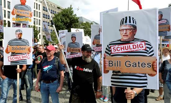 """הפגנת מכחישי הקורונה בברלין. על תמונות של ביל גייטס במדי אסיר כתוב """"אשם"""" / צילום: Michael Sohn, AP"""