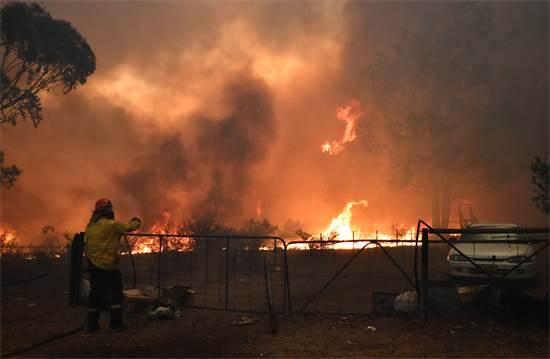 כבאי מנסה לכבות שריפה / צילום: STRINGER, רויטרס