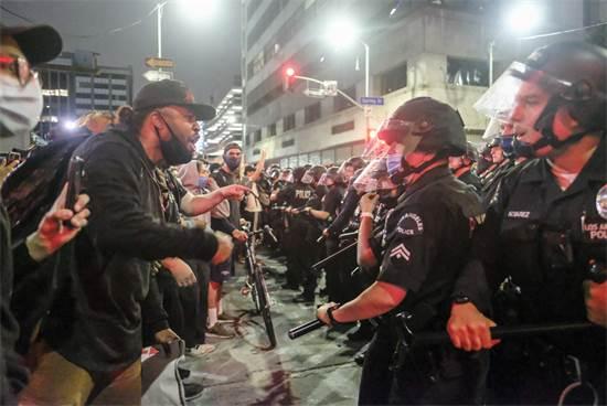 מפגינים ושוטרים בלוס אנג'לס ביום שישי / צילום: Ringo H.W. Chiu, AP