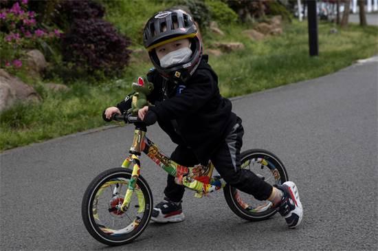 ילד סיני עם מסכה רוכב על אופניים בווהאן / צילום: NG Han Guan, AP