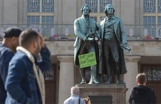 """אלמונים הציבו שלט על אנדרטה בגרמניה, שבו נכתב: """"הישארו בריאים ותישארו בבית"""" / צילום: Jens Meyer, AP"""