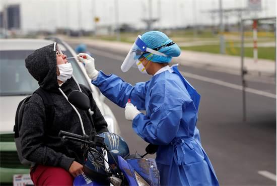 אחות מבצעת בדיקת קורונה לאדם על אופנוע בפרגוואי / צילום: AP