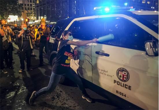 מפגינה בלוס אנג'לס משחיתה מכונית משטרה ביום שישי  / צילום: Ringo H.W. Chiu, AP