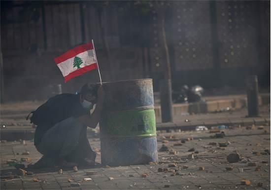 מפגין בביירות מוצא מחסה בעת הפגנה נגד השלטון / צילום:  Hannah McKay, רויטרס