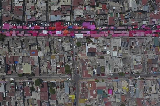 סדינים ובדים ורודים מגנים מהשמש על דוכני השוק במקסיקו סיטי / צילום: Rebecca Blackwell, AP