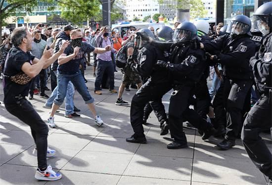 מפגינים מתעמתים עם שוטרים במהלך ההפגנה שהתקיימה אתמול בברלין / צילום: Christian Mang, רויטרס