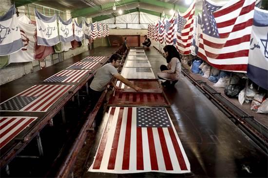 """עובדים איראניים מדפיסים דגלי ארה""""ב וישראל שמיועדים לשריפה / צילום: Ebrahim Noroozi, AP"""