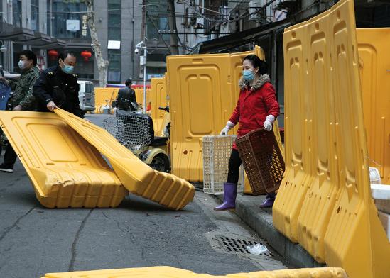 מפרקים את הגדר שהוצבה בווהאן. החיים שבים לסדרם / צילום: Ng Han Guan, Associated Press