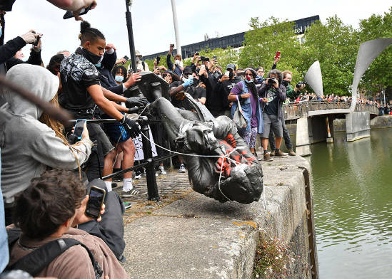 פסל של סוחר העבדים אדוורד קולסטון, מגולגל לנהר בבריסטול בבריטניה, בשבוע שעבר. מחאת הפסלים סחפה גם את אירופה / צילום: J. Scott Applewhite, Associated Press