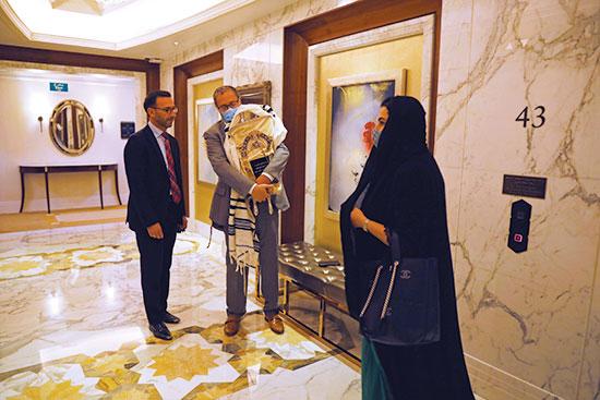 חבר הקהילה היהודית בדובאי אוחז ספר תורה בבית מלון בעיר / צילום: Nir Elias, Associated Press