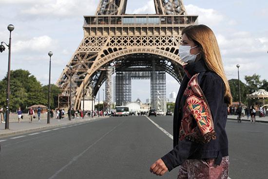 הולכת רגל ליד האייפל. מדינות רבות שינו את דעתן ואימצו את המסכות  / צילום: Francois Mori, Associated Press