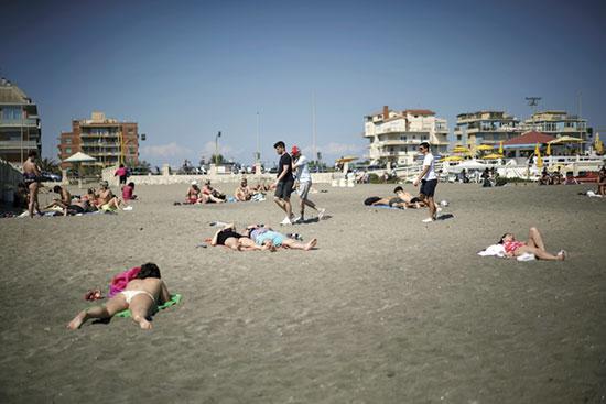 הקיץ מגיע והאיטלקים יצאו לים. האם החום יחסל את הנגיף? / צילום: Andrew Medichini, AP