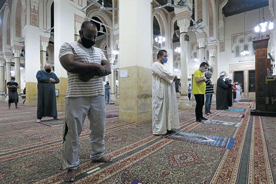 מתפללים עוטי מסכות במסגד בקהיר / צילום: Mohamed Abd El Ghany, רויטרס