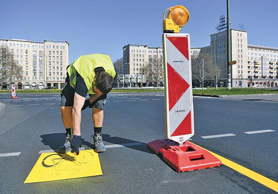 עובד עירייה מסמן על הכביש סימון לשביל אופניים. ברלין, גרמניה / צילום: רויטרס