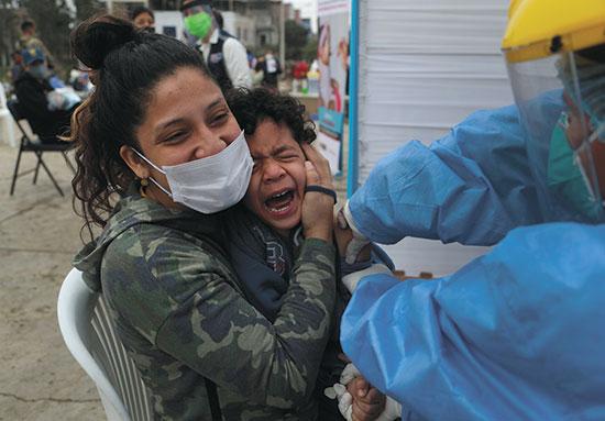 ילד מתחסן במבצע חיסונים ארצי בפרו, יוני / צילום: Martin Mejia, Associated Press