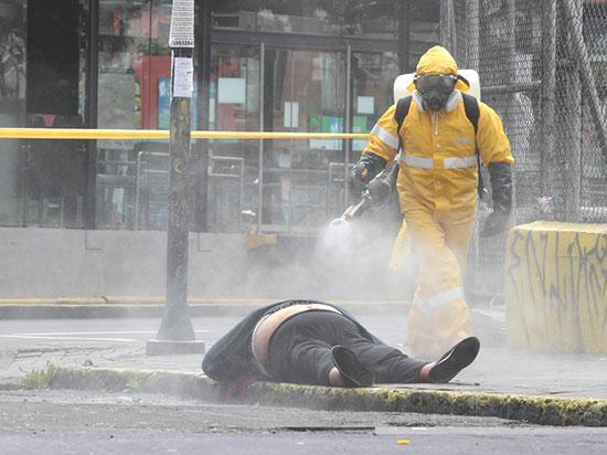 עובד מדינה מחטא גופת אשה שמתה מקורונה ונזנחה ברחוב בקיטו באקוודור, החודש / צילום: Dolores Ochoa, Associated Press