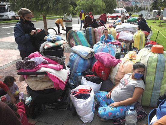 מהגרי עבודה מוונצואלה בקולומביה ממתינים לאוטובוס לחזור לביתם, בשבוע שעבר / צילום: Fernando Vergara, Associated Press