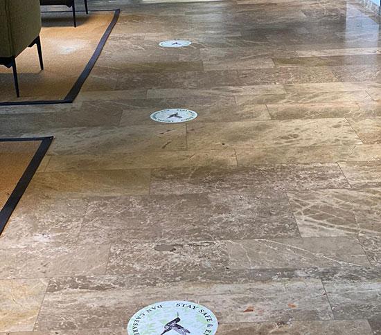 מדבקות לשמירת מרחק רצוי בלובי המלון / צילום: דוברות מלונות דן