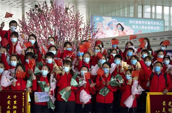 עובדים רפואיים ממחוז ג'ילין בסין מנופפים בדגלים סיניים כשהם מתכוננים לחזור הביתה בשדה התעופה הבינלאומי ווהאן / צילום: AP
