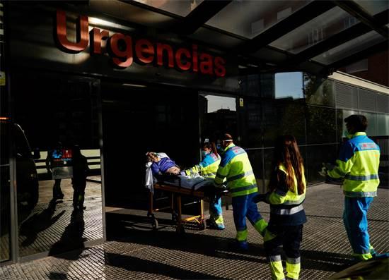 """צוות רפואי מביא אדם חולה בקורונה לביה""""ח במדריד / צילום: Juan Medina, רויטרס"""