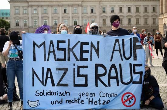 """הפגנה נגד הפגנת מתנגדי החיסונים והקורנה. בשלט כתוב: """"סולידריות נגד מכחישי קורונה ושנאה מצד הימין הקיצוני"""" / צילום: Christophe Gateau/dpa, AP"""