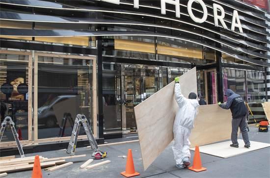 עובדים אוטמים את חלונות הראווה של חנות ספורה בניו יורק / צילום: Mary Altaffer, AP